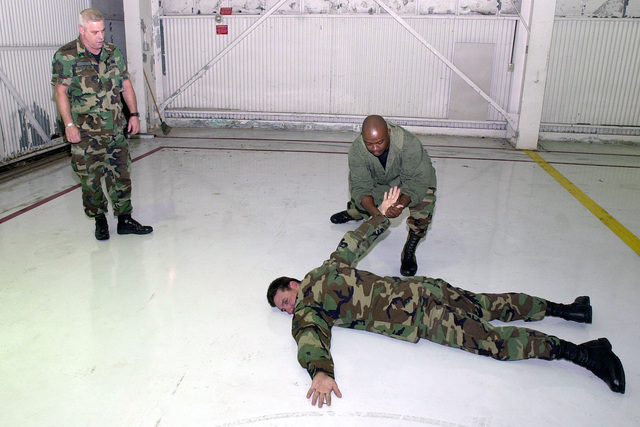 In preparation for Operation ENDURING FREEDOM, Technical Sergeant Mike Masden, USAF, of the 138th Fighter Wing prepares to handcuff an individual during a Security Force augmentee training class as augmentee instructor SENIOR MASTER Sergeant Mike Stapleton, USAF, (left) observes his technique. All are members of the 138th Fighter Wing, Tulsa Air National Guard, Tulsa Oklahoma. ENDURING FREEDOM is in support of the Global War on Terrorism (GWOT), fighting terrorism abroad