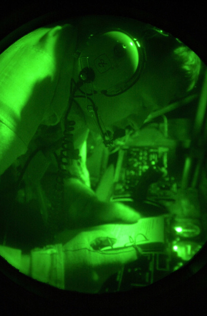Viewed through the green glow of a night scope, STAFF Sergeant Max Morkin, a boom operator from the 319th Air Refueling Squadron, 319th Air Expeditionary Group (AEG), uses the dim red nightlights to finalize his refueling checklist, prior to a night aerial refueling of an E-C3 (AWACS). The 319th AEG deployed to a classified location in support of Operation ENDURING FREEDOM, which is in support of the Global War on Terrorism (GWOT), fighting terrorism abroad