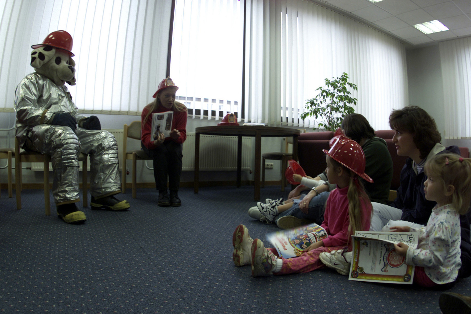 """Rentia Jones (far right), a Library Technician at Spangdahlem AB, Germany and """"Sparky the Fire Dog"""" read stories to elementary school children and parents during a fire prevention awareness program, sponsored by the 52nd Civil Engineers Squadron, at Spangdahlem AB, Germany"""