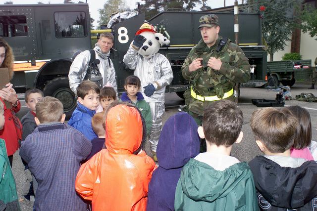 STAFF Sergeant (SSGT) Jason Theriault, USAF, (far right), Sparky the dog, and AIRMAN First Class (A1C) Stan Bucks, USAF, 52nd Civil Engineering Squadron (CES), talks to Mrs. Nicoley's First Graders at Spangdahlem AB, Germany, during the Fire Prevention Week 7-13 October, about fire safety