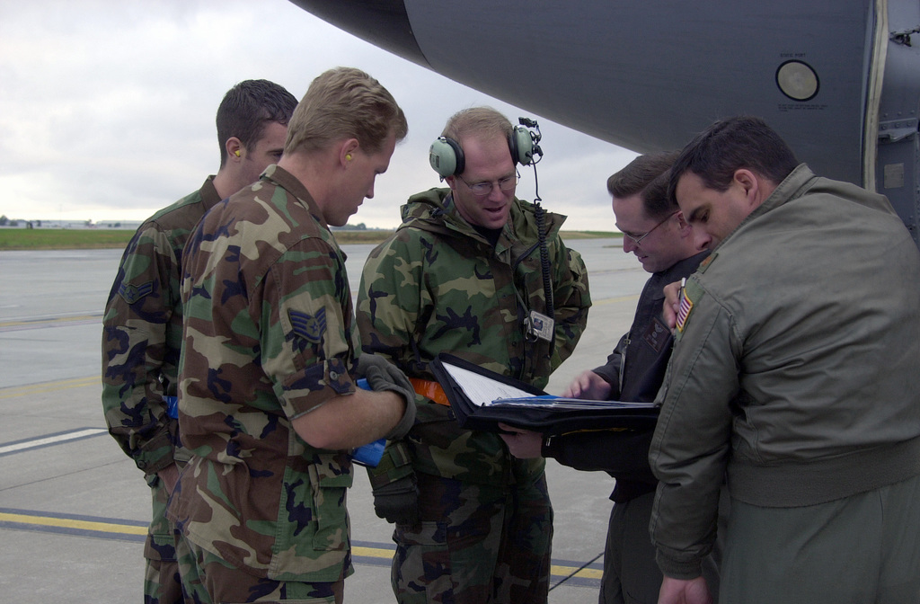 At Lincoln Municipal Airport, STAFF Sergeant Cory Wacker, USAF, (left, front), AIRMAN First Class Douglas Chadwick, USAF, (left) and Technical Sergeant Sam Rienke, USAF, (center back) go over the aircraft maintenance records with Major Steve Burke. USAF, (right front) and Captain John Williams, USAF, before embarking onto the KC-135R on a refueling training mission. All are with the 155th Air Refueling Wing, Nebraska Air National Guard