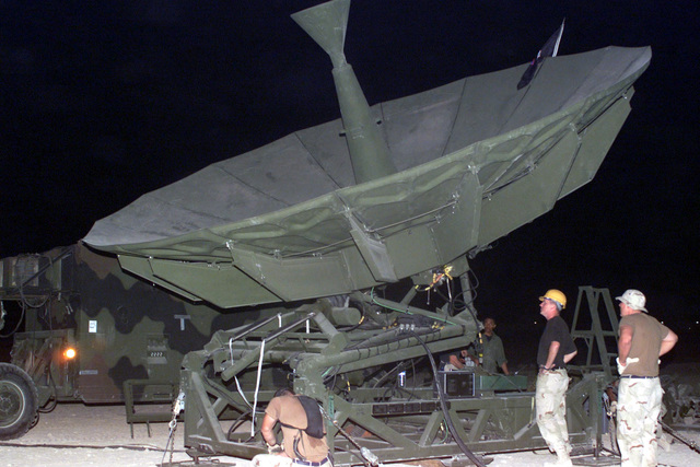 Members of the 228th Combat Communications Squadron, McGhee Tyson Air National Guard Base, Tennessee look on as their OE-361 Quick Reaction Satellite Antenna (QRSA) is raised into position during Operation ENDURING FREEDOM. In response to the terrorist attacks on September 11, 2001 at the New York World Trade Center and the Pentagon, President George W. Bush initiated Operation ENDURING FREEDOM in support of the Global War on Terrorism (GWOT), fighting terrorism abroad