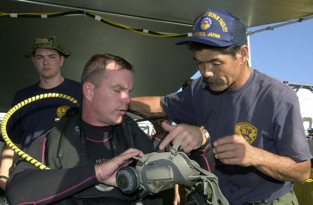 Onboard the Crowley Marine 450-10 Barge, Mr. Koji Hiramura (right) from the US Navy (USN) Ship Repair Facility in Yokosuka, Japan, assists CHIEF Warrant Officer (CWO) Robert Cassles, from Mobile Diving Salvage Unit One (MDSU-1), with his diving suite, in preparing for the first scuba dive on the Japanese fishing vessel Ehime Maru after it was relocated to a shallow water site