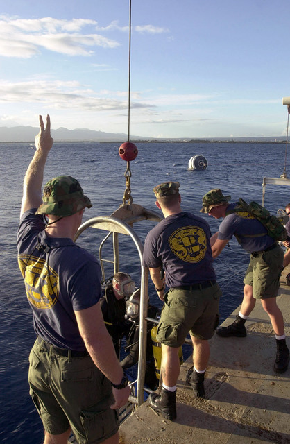 Onboard the Crowley Marine, 450-10 Barge US Navy (USN) divers assigned to Mobile Diving Salvage Unit One (MDSU-1), enter the water aboard a diving stage, in preparing for the first scuba dive on the Japanese fishing vessel, Ehime Maru after it was relocated to a shallow water site