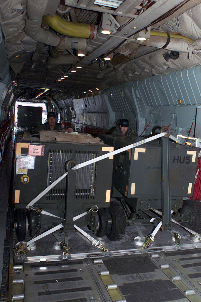 MASTER Sergeants Ric Bass, (left), and Al Murguia, both with the 730th Airlift Squadron from March Air Reserve Base, California, push a pallet into position onboard a C-141C Starlifter that will transport a cargo load from Christchurch, New Zealand, to McMurdo Station in Antarctica during Operation DEEP FREEZE 2001
