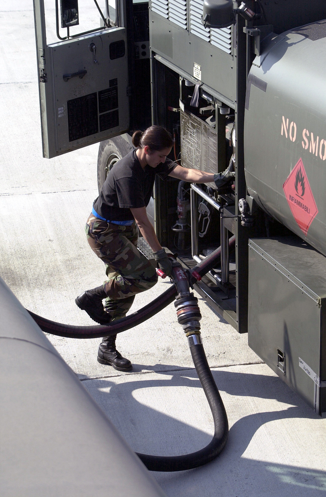 STAFF Sergeant Julia Nelson, US Air Force (USAF), fuels specialist, 375th Logistics Support Squadron, Scott Air Force Base, Illinois, reels in the refueling hose back into her R-11 fuel truck after filling up a C-17 Globemaster at Naval Air Station Sigonella, Italy, during Operation ENDURING FREEDOM. In response to the terrorist attacks on September 11, 2001 at the New York World Trade Center and the Pentagon, President George W. Bush initiated Operation ENDURING FREEDOM in support of the Global War on Terrorism (GWOT), fighting terrorism abroad