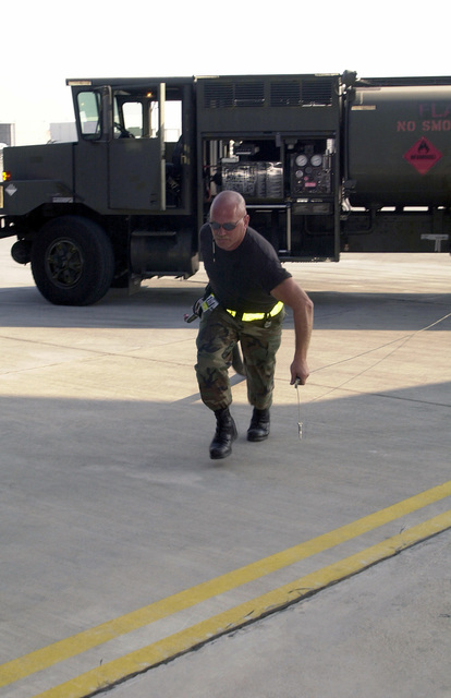 Technical Sergeant T. J. Theis, US Air Force (USAF), fuels specialist, 96th Supply Squadron, Eglin Air Force Base, Florida, drags out the fuel hose and grounding cord from his R-11 fuel truck, toward an aircraft on the ramp at Naval Air Station (NAS) Sigonella, Italy, during Operation ENDURING FREEDOM. In response to the terrorist attacks on September 11, 2001 at the New York World Trade Center and the Pentagon, President George W. Bush initiated Operation ENDURING FREEDOM in support of the Global War on Terrorism (GWOT), fighting terrorism abroad
