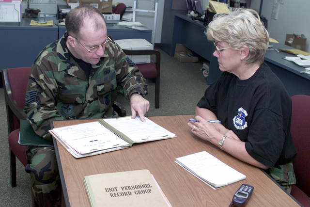 US Air Force (USAF) Technical Sergeant (TSGT) Gregory Bruno (left), 149th Security Forces Squadron (SFS), 149th Fighter Wing (FW), and USAF SENIOR MASTER Sergeant (SMSGT) Debra Powley, Military Personnel Flight, review TSGT Brunos personnel records at Lackland Air Force Base, Texas (TX) before he departs on a short Temporary Duty Assignment (TDY), in support of Homeland Defense