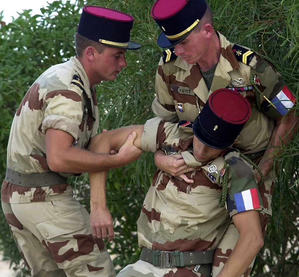 A French Army Soldier is carried to a shaded area after he fainted from standing at attention, while attending the Battle of El Alamein Memorial Ceremony, during Exercise BRIGHT STAR 01/02. The Ceremony commemorated the battle between axis and allied forces for the control of Egypt during WW II. Participants in the Bright Star Exercise took time out to attend the Memorial Ceremony. BRIGHT STAR 01/02 is a multinational exercise involving more than 74,000 troops from 44 countries that enhances regional stability and military-to-military cooperation among our key allies, and our regional partners. It prepares US Central Command to rapidly deploy and employ the forces needed to deter...