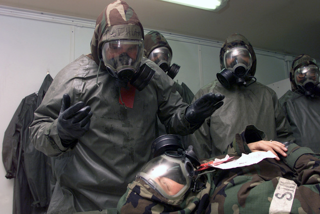 Technical Sergeant (TSGT), Tim Hutter (left), USAF, 51st Medical Group, Osan AB, Korea explains the decontamination process to the patient, SENIOR AIRMAN (SRA) Lisa Love, USAF, 25TH Fighter Squadron, Crew CHIEF during the Initial Response Readiness Exercise/Combat Employment Readiness Exercise (IRRE/CERE) at Osan AB, Korea. All members of the decontamination team are wearing Mission Oriented Protective Posture response level 4 (MOPP-4) gear