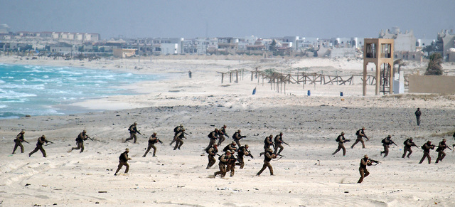 A wide angle view of the beach and staging area at El Omayed, Egypt as USMC personnel assigned to the 26TH Marine Expeditionary Unit (MEU), Special Operation Capable (SOC), Camp Lejeune, NC practice beach assault exercises, while conducting amphibious operations during Exercise BRIGHT STAR 01/02. BRIGHT STAR 01/02 is a multinational exercise involving more than 74,000 troops from 44 countries that enhances regional stability and military-to-military cooperation among our key allies, and our regional partners. It prepares US Central Command to rapidly deploy and employ the forces needed to deter aggressors and, if necessary, fight and win side-by-side with our allies and regional partners