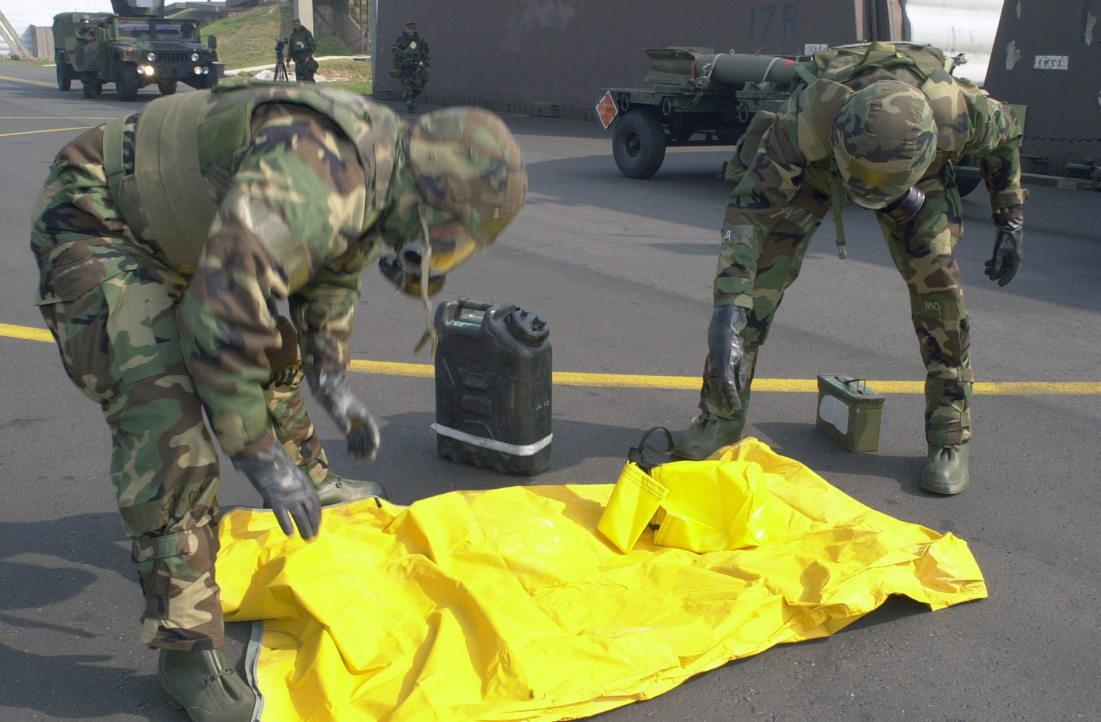 SENIOR AIRMAN (SRA), Joe Deslauriers, and SRA Brian Borrero both, USAF, 51st Civil Engineer Squadron dressed in Mission Oriented Protective Posture response level 4 (MOPP-4) gear, prepare to set up a decontamination wash station during the Initial Response Readiness Exercise/Combat Employment Readiness Exercise (IRRE/CERE) at Osan AB, Korea