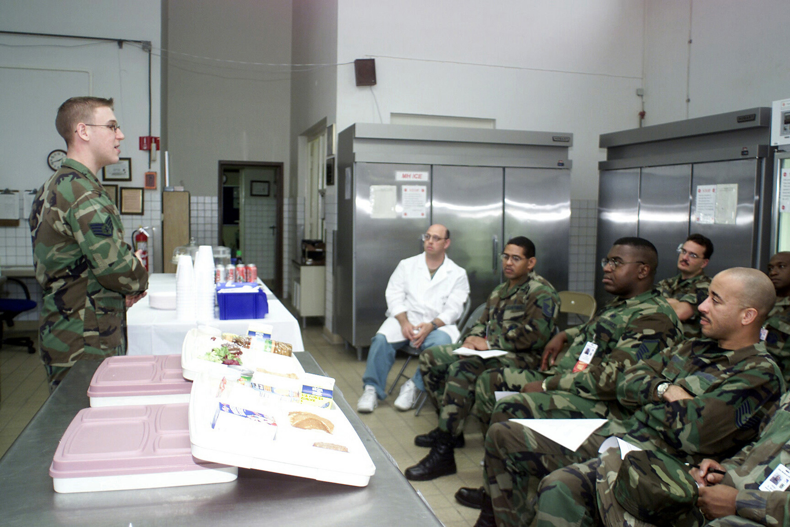 STAFF Sergeant (SSGT) Jason Herman, Diet Therapy Journeyman assigned to the 52d Medical Support Squadron, Spangdahlem AB, Germany displays two patient food tray samples to staff members, during a monthly ethnic food quality assurance test