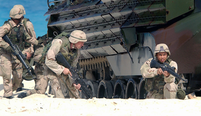 USMC personnel assigned to the 26TH Marine Expeditionary Unit (MEU), Camp Lejeune, NC armed with a 5.56mm M16A2 assault rifles, takes up defensive positions near an Amphibious Assault Vehicle (AAV7A1) on the beach at El Omayed, Egypt while conducting amphibious operations, during Exercise BRIGHT STAR 01/02. BRIGHT STAR 01/02 is a multinational exercise involving more than 74,000 troops from 44 countries that enhances stability and military-to-military cooperation among our key allies, and our partners. It prepares US Central Command to rapidly deploy and employ the forces needed to deter aggressors and, if necessary, fight and win side-by-side with our allies and...