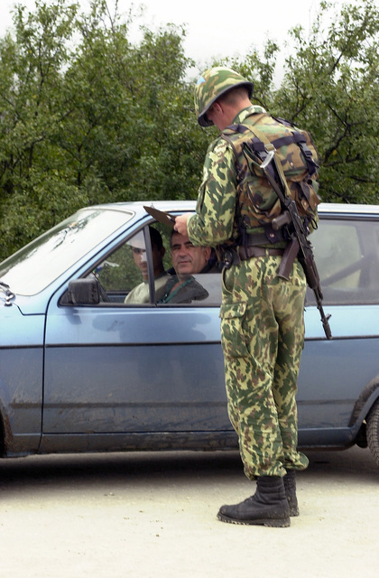 A Russian soldier with the 13th Tactical Group, checks a civilian stopped at Checkpoint 75 in the East sector of Kosovo, jointly guarded by American and Russian soldiers to check incoming and outgoing traffic, in support of Operation JOINT GUARDIAN II