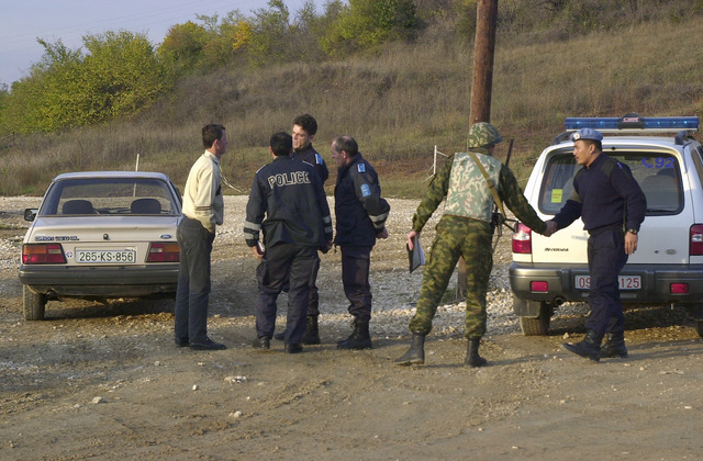 A Russian soldier with the 13th Tactical Group (TG) talks to the local police in the East sector of Kosovo