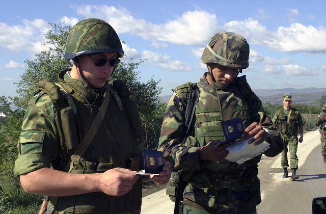 An American soldier with the 1ST Battalion, 41st Field Artillery (1-41 FA) and a Russian soldier with the 13th Tactical Group, check the license of a civilian stopped at Checkpoint 75, in the East sector of Kosovo, in support of Operation JOINT GUARDIAN II