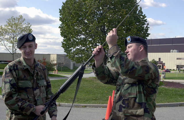 "Prior to entering the Dining Facility, for a briefing, at Stewart Air National Guard Base, Sergeant Jeff Davis, USA, performs a ""Rodding"" check (checking the barrel all the way to the breach to make sure there is no round loaded in the weapon) on Private First Class Fierro's weapon. Both are with the New York Army National Guards 27th Separate Infantry Brigade (Enhanced) and are in the second rotation of New York Guard personnel to be trained by the Federal Aviation Administration (FAA) in airport security operations. As part of Operation NOBLE EAGLE, the Guard personnel will perform security missions at 19 commercial airports and four separate nuclear power sites around the state. NOBLE ..."