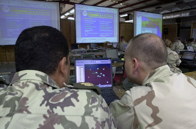 Egyptian Army, Major (MAJ), Medht Elessawi (left) and MAJ, Charles McClean, USAF, assigned to the US Central Command, MacDill AFB, FL work on computer simulated war games during the Command Post Exercise (CPX) at Mubarak Military City`s Coalition Operations Center during Exercise BRIGHT STAR 01/02. BRIGHT STAR 01/02 is a multinational exercise involving more than 74,000 troops from 44 countries that enhances regional stability and military-to-military cooperation among our key allies, and our regional partners. It prepares US Central Command to rapidly deploy and employ the forces needed to deter aggressors and, if necessary, fight and win side-by-side with our allies and regional partners