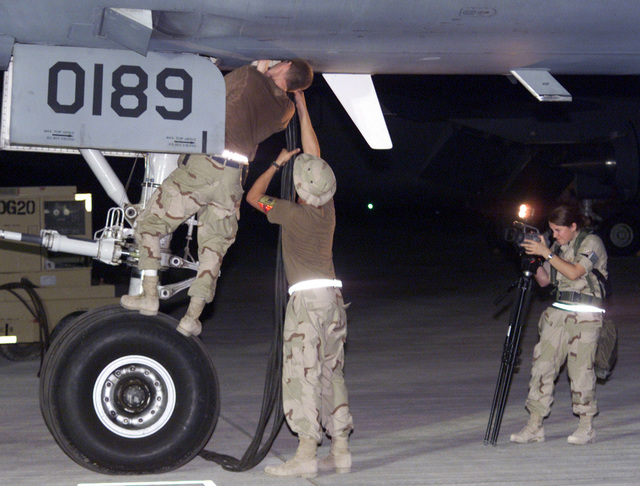 AIRMAN Michelle Gaudin, USAF, 509th Communications Squadron, documents two members of the 660th Aircraft Generation Squadron, Travis AFB, California, attaching an external power cable to a KC-10 Extender refueling aircraft while deployed to the Persian Gulf region in support of Operation ENDURING FREEDOM. In response to the terrorist attacks on September 11, 2001 at the New York World Trade Center and the Pentagon, President George W. Bush initiated Operation ENDURING FREEDOM in support of the Global War on Terrorism (GWOT), fighting terrorism abroad