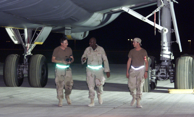 Members of the 660th Aircraft Generation Squadron, Travis AFB, California, discuss the status of this KC-10 Extender refueling aircraft. They and aircraft are deployed to a base in the Persian Gulf in support of Operation ENDURING FREEDOM. In response to the terrorist attacks on September 11, 2001 at the New York World Trade Center and the Pentagon, President George W. Bush initiated Operation ENDURING FREEDOM in support of the Global War on Terrorism (GWOT), fighting terrorism abroad