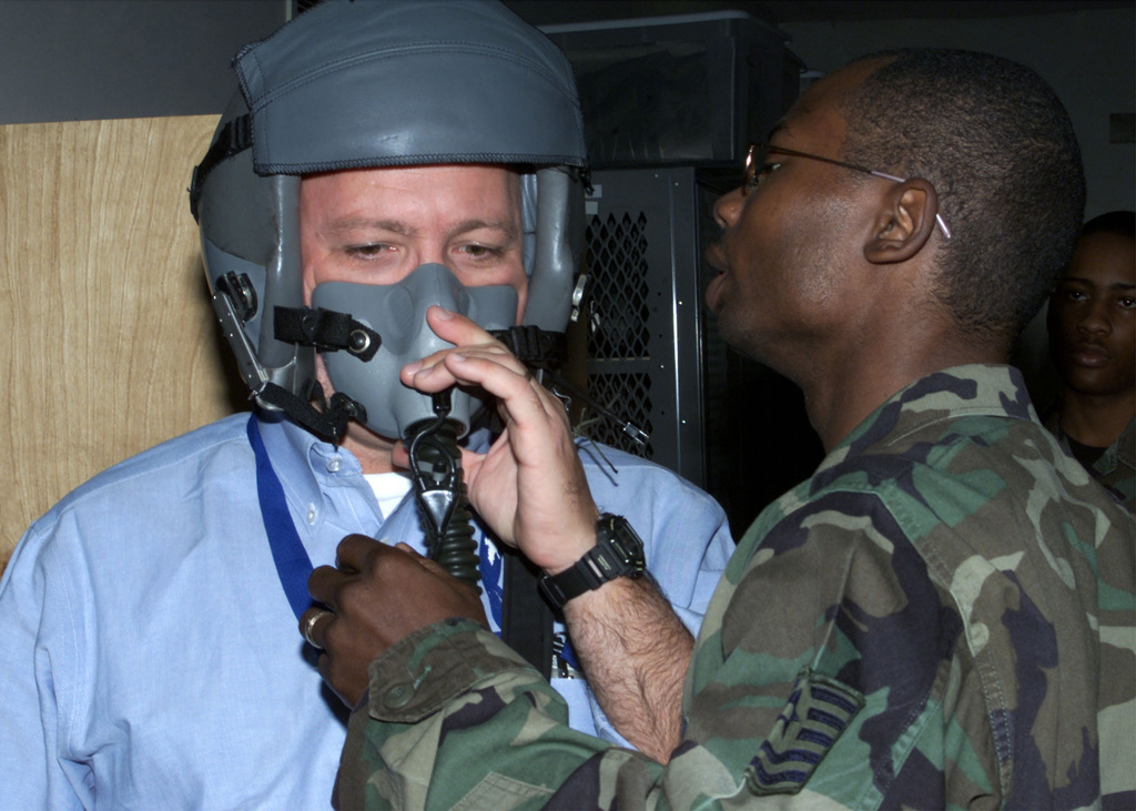 Inside the life support section for the 20th Bomb Squadron, Barksdale AFB, LA Technical Sergeant (TSGT), Randy Taylor, USAF makes adjustments to a helmet worn by Mr. Al Henkel, Correspondent with NBC News. Mr. Henkel is scheduled to make an incentive flight aboard an USAF B-52H Stratofortress aircraft. The NBC News crew was scheduled to broadcast live from Barksdale AFB, LA, for the Today Show