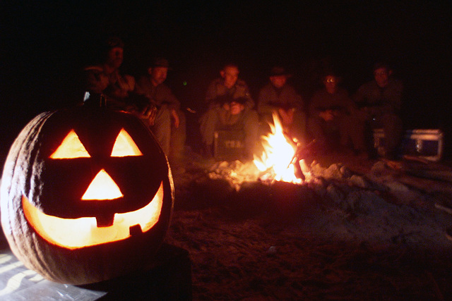 A jack o' lantern, glows brightly on Halloween night at Camp Barkeley, as USAF students gather around the fire at Camp Barkeley, during the Aircrew Life Support Instructor Course at Dyess AFB, Texas (TX)
