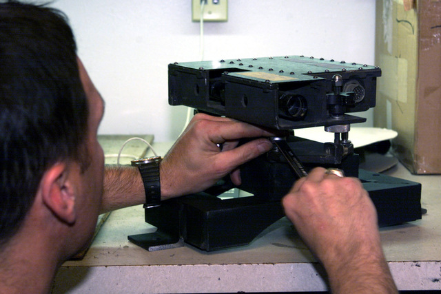 Civilian Dwayne Davidson, Raytheon technician, makes an adjustment to the modified bracket of the targeting mechanism for the B1 Centauro wheeled tank destroyer. Modification is to correct foresight alignment irregularities. Fort Lewis, Washington