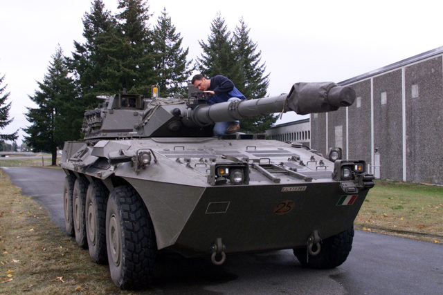 Civilian Dwayne Davidson, Raytheon technician, makes an adjustment to the targeting mechanism, with a modified bracket to correct foresight alignment irregularities, mounted on the barrel of the 105 mm gun on a B1 Centauro (8 X 8) wheeled tank destroyer, small Italian Flag painted on front of vehicle. Fort Lewis, Washington