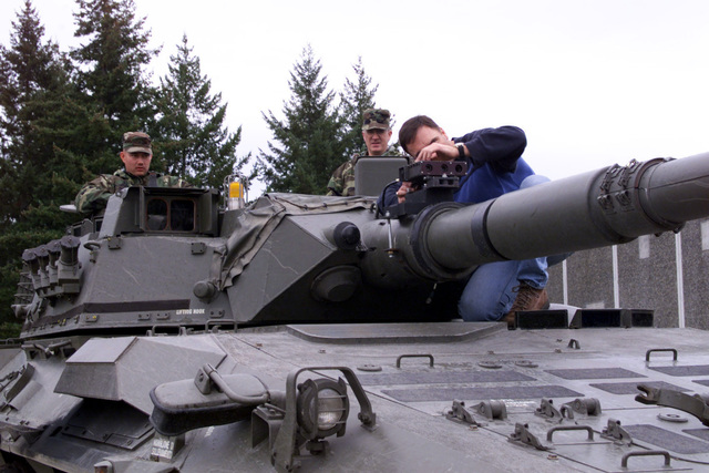 Civilian Dwayne Davidson, Raytheon technician, makes an adjustment to the targeting mechanism, with a modified bracket to correct foresight alignment irregularities, mounted on the barrel of the 105 mm gun on a B1 Centauro (8 X 8) wheeled tank destroyer. Observing are US Army Sergeant (SGT) Emil Woppel (left) and STAFF Sergeant Mike Garback (right), Company B, 2nd Battalion, 3rd Infantry Regiment, 3rd Brigade, 2nd Infantry Division. Fort Lewis Washington