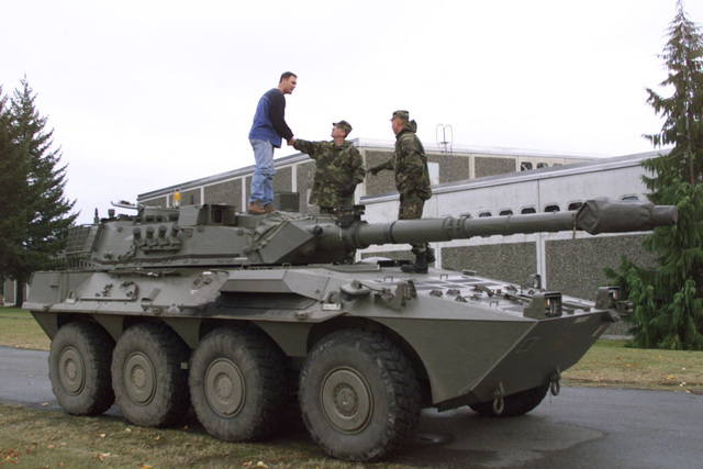 Standing on top of a B1 Centauro (8 X 8) wheeled tank destroyer, civilian Dwayne Davidson, a Raytheon technician (left), shakes hands with US Army STAFF Sergeant Mike Garback (center), Company B, 2nd Battalion, 3rd Infantry Regiment, 3rd Brigade, 2nd Infantry Division. Sergeant (SGT) Emil Woeppel, Company B is on the right. A targeting mechanism, with a modified bracket to correct foresight alignment irregularities, is mounted on the barrel of the 105 mm gun. A small Italian Flag is painted on front of vehicle. Fort Lewis Washington