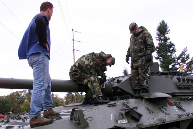 US Army STAFF Sergeant Mike Garback (center left) and Sergeant (SGT) Emil Woppel (center, right), Company B, 2nd Battalion, 3rd Infantry Regiment, 3rd Brigade, 2nd Infantry Division attach a modified bracket, to correct foresight alignment irregularities, to the barrel of the 105 mm gun on a B1 Centauro (8 X 8) wheeled tank destroyer. Observing are civilian Dwayne Davidson, Raytheon technician (left) and First Lieutenant (1LT) James Anderton, Company B. Fort Lewis, Washington