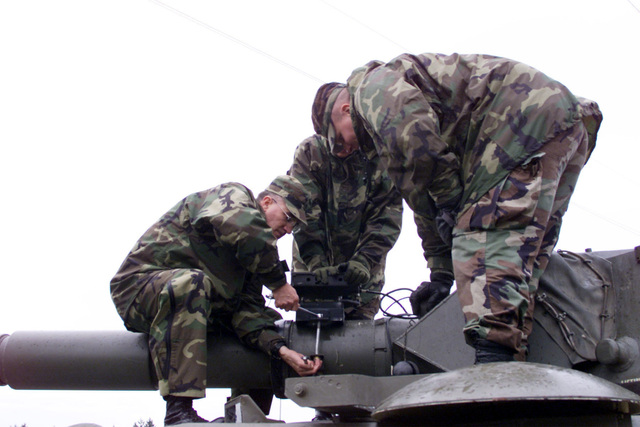 US Army STAFF Sergeant Mike Garback (left), Sergeant (SGT) Emil Woppel (center) and First Lieutenant (1LT) James Anderton (right), Company B, 2nd Battalion, 3rd Infantry Regiment, 3rd Brigade, 2nd Infantry Division attach a modified bracket, to correct foresight alignment irregularities, to the barrel of the 105 mm gun on a B1 Centauro (8 X 8) wheeled tank destroyer. Fort Lewis, Washington