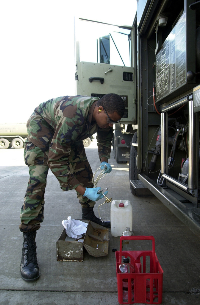SENIOR AIRMAN Sean Willis, USAF, fuels specialist, 375th Logistics Support Squadron, Scott AFB, Illinois, prepares to take fuel samples from an R-11 fuel truck for testing at Naval Air Station, Sigonella, Sicily. Air Force members are deployed to Naval Air Station Sigonella in support of Operation ENDURING FREEDOM
