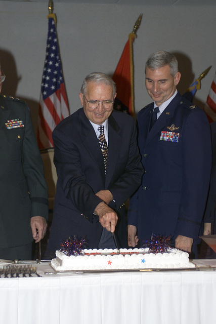 US Army (USA) Retired MASTER Sergeant (MSG) Audrey Harris cuts the first piece of cake during the base Retiree Appreciation Day opening ceremony at Little Rock AFB, Arkansas (AR). US Air Force (USAF) Colonel (COL) David J. Scott, Commander 314 Airlift Wing looks on
