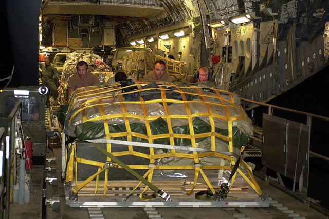 Members of the 615th Tanker Airlift Control Element from Travis AFB, CA, off-load pallets of equipment from a C-17 Globemaster III. The C-17 is from Charleston AFB, South Carolina. Members are the 615th TALCE are forward deployed to several classified locations providing command and control support of all assets inbound in support of Operation ENDURING FREEDOM. Operation ENDURING FREEDOM is in support of the Global War on Terrorism (GWOT), fighting terrorism abroad, after the terrorist attacks on September 11, 2001 at the New York World Trade Center and the Pentagon
