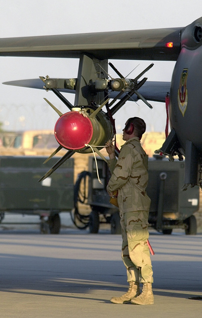A ground crewman readies a 332nd Air Expeditionary Group active duty F-15E Strike Eagle from Mountain Home Air Force Base (AFB), Idaho, flown by a reserve pilot from Luke AFB, Arizona. On the wing of the Eagle is a GBU-24 Paveway III 2000-pound bomb and above it is an AIM-9 Sidewinder
