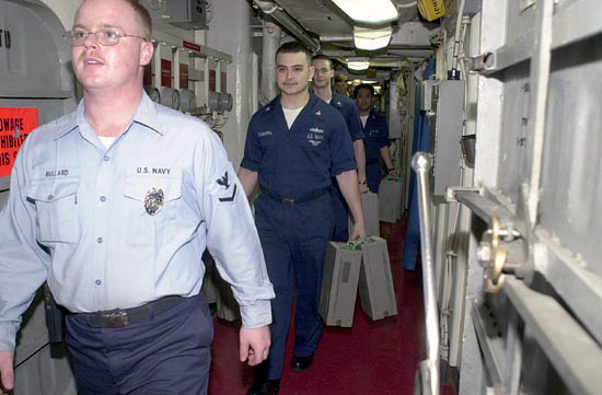 A US Navy (USN) PETTY Officer Third Class (PO3) MASTER-at-Arms (MA3) provide armed security for sailors assigned to the supply department S-4 division (disbursing), as they carry money to the automated teller machine, aboard the Aircraft Carrier USS KITTY HAWK (CV-63)