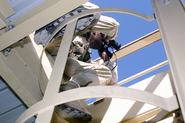 MASTER Sergeant Kevin Scales, USAF, 366th Security Forces Squadron (deployed) scans the base perimeter through binoculars from the top of a watchtower during Operation ENDURING FREEDOM. In response to the terrorist attacks on September 11, 2001 at the New York World Trade Center and the Pentagon, President George W. Bush initiated Operation ENDURING FREEDOM in support of the Global War on Terrorism (GWOT), fighting terrorism abroad