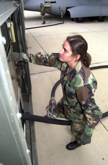 STAFF Sergeant Julia Nelson, USAF, 375th Logistics Support Squadron, Scott AFB, Illinois, reels in a fueling hose back into her R-11 fuel truck after fueling a C-17A Globemaster III during deployment in support of Operation ENDURING FREEDOM, from Naval Air Station, Sigonella, Sicily