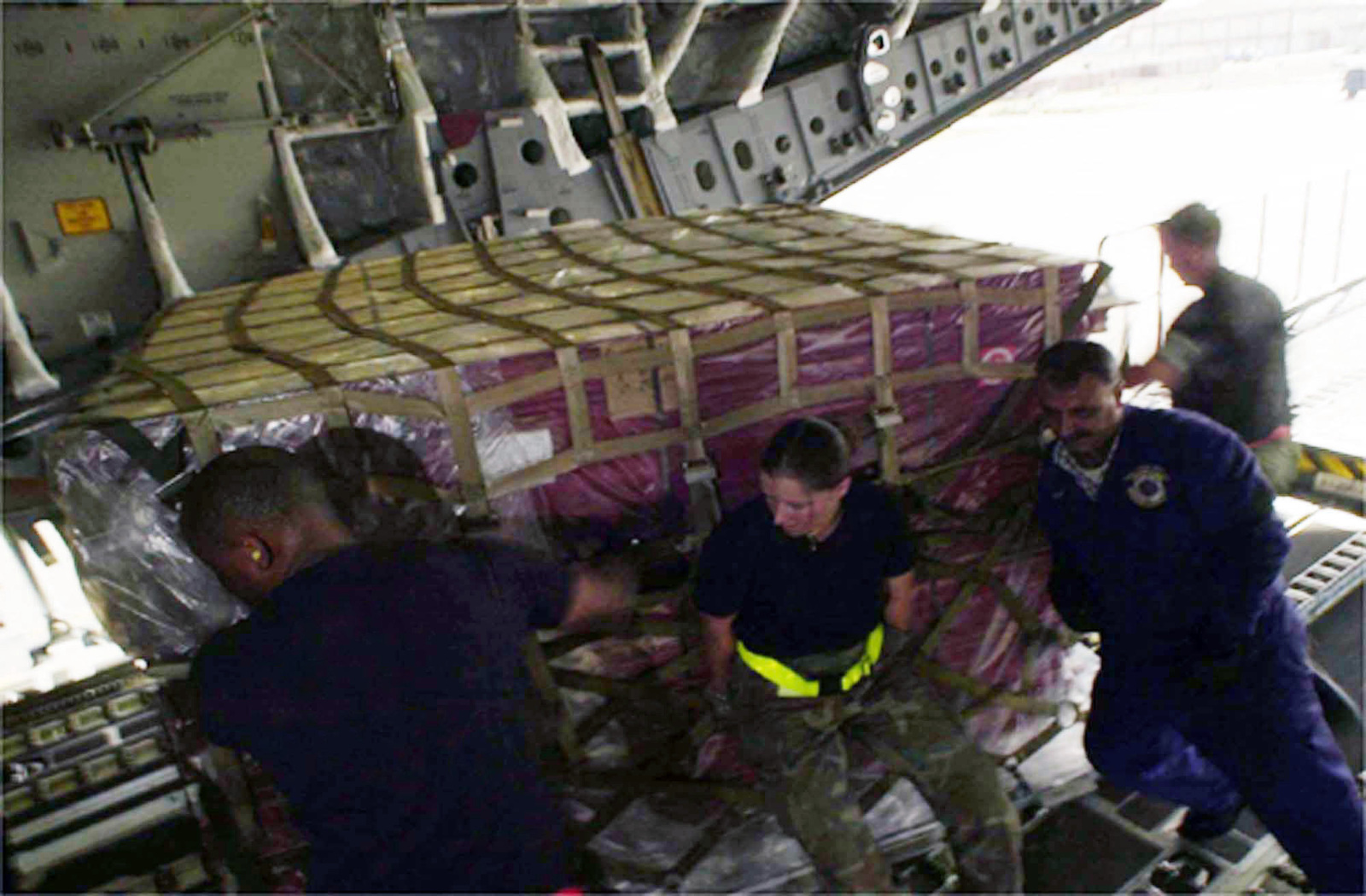US Air Force (USAF) Airmen assigned to the 728th Air Mobility Squadron (AMS) and host country nationals load palletized cargo onto a C-17A Globemaster III aircraft, while deployed at a forward location in support of Operation ENDURING FREEDOM. (Substandard image)