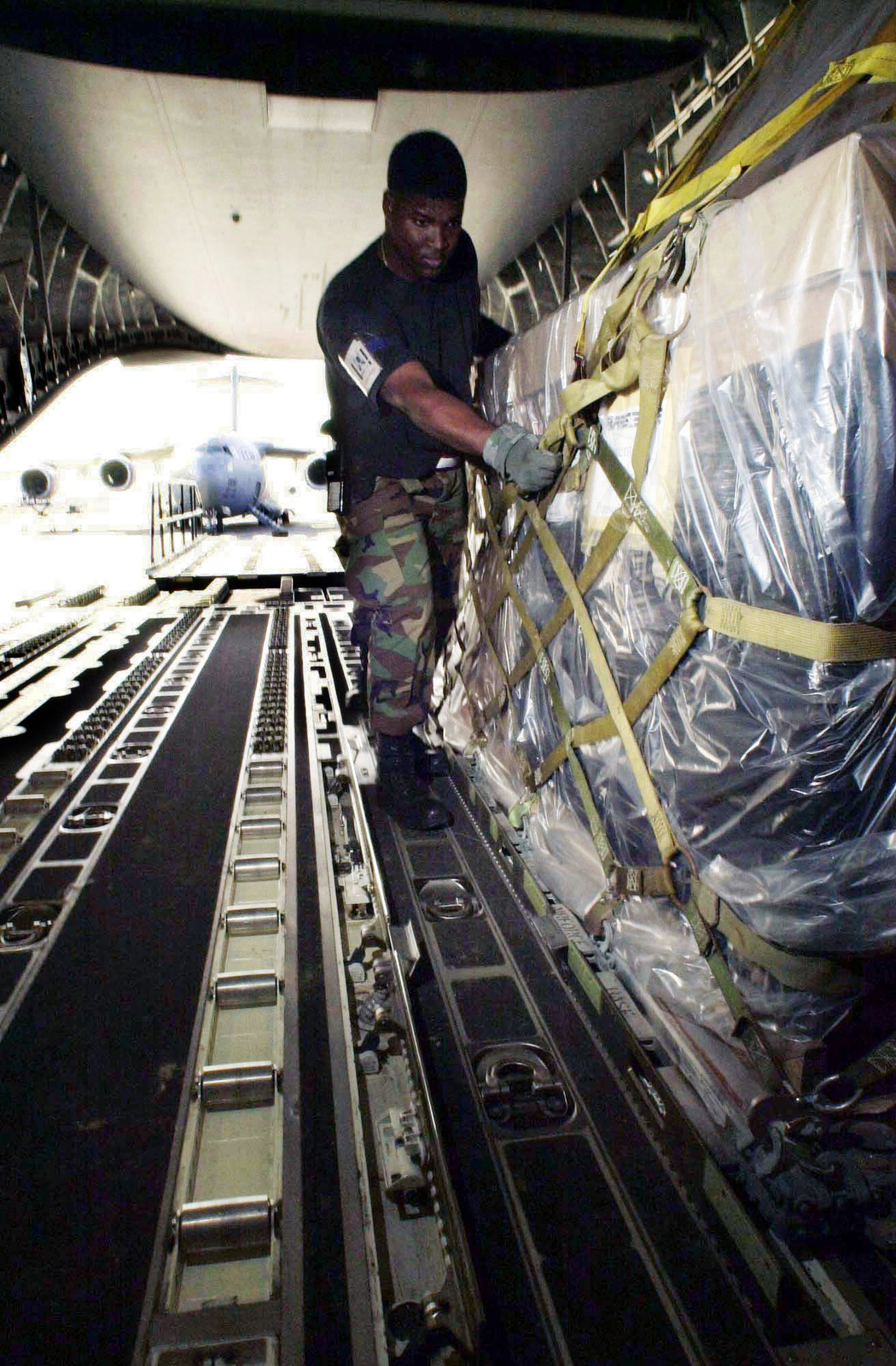 US Air Force (USAF) SENIOR AIRMAN (SRA) Lowell Pointer, 728th Air Mobility Squadron (AMS) loads palletized cargo onto a C-17A Globemaster III aircraft, while deployed at a forward location in support of Operation ENDURING FREEDOM