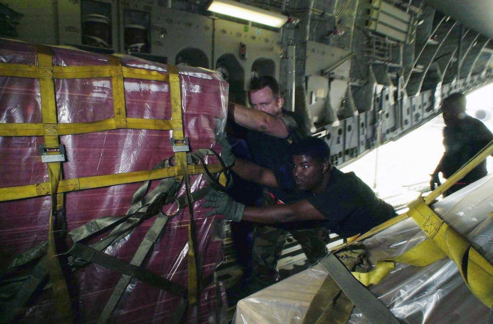 US Air Force (USAF) SENIOR AIRMAN (SRA) Lowell Pointer (left) and USAF STAFF Sergeant (SSGT) Jeffrey Mount, both assigned to the 728th Air Mobility Squadron (AMS) load palletized cargo onto a C-17A Globemaster III aircraft, while deployed at a forward location in support of Operation ENDURING FREEDOM