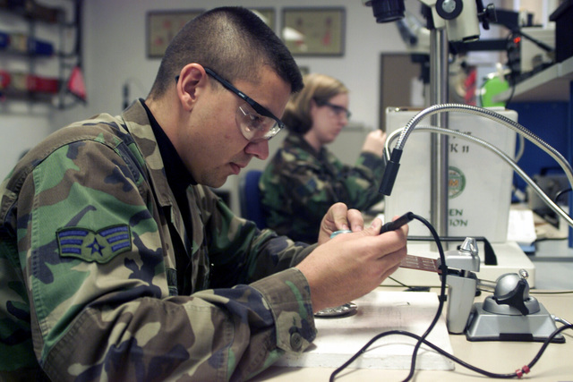 SENIOR AIRMAN (SRA) Agustin R. Nazario (foreground) and SRA Jennifer C. Hanaway both assigned to the 31st Maintenance Squadron, Avaino AB, Italy work on circuit card assemblies while participating in the Micro Miniature/Miniature Electronic Repair Program, offered by Detachment 17 of the 372nd Training Squadron at Spangdahlem AB, Germany
