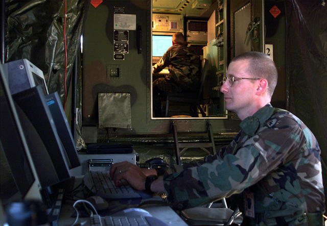 US Army (USA) Sergeant First Class (SFC) Daniel Massie, Brigade Subscriber Node (BSN) operator, works on the Integrated Network Management (INM) systems, as a second operator works inside the Standard Integrated Command Post Shelter (SICPS) shelter, inside the BSN test site at Fort Gordon, GA