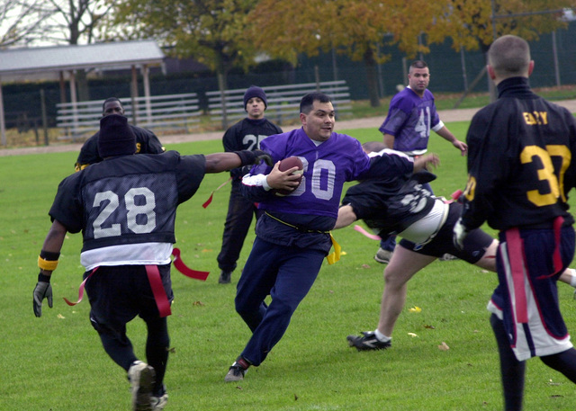 CHIEF MASTER Sergeant (CMSGT), Manuel Solis, USAF, 100th Security Forces Squadron, Royal Air Force (RAF) Mildenhall, UK dodges tacklers in the Turkey Bowl flag football game held at Ford Park. Due to recent world events the regular flag football season was cancelled. The 100th Services Squadron at RAF Mildenhall came up with a tournament to give the players an opportunity to participate. The 100th Security Forces Squadron beat the 100th Maintenance Squadron 13-0, in the tournamentschampionship game known as the Turkey Bowl