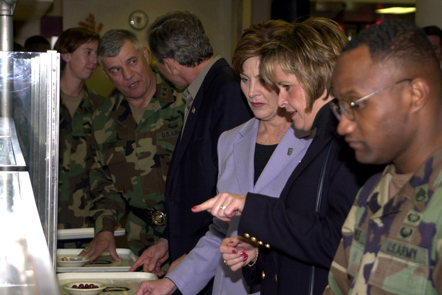 Mrs. Vicki Cody, wife of US Army (USA) Major General (MGEN) Richard A. Cody, Commander, 101st Airborne Division (Air Assault), gives First Lady, Mrs. Laura Bush, tips on what is on the menu at the Aviation Dining Facility, as US President George W. Bush and MGEN Cody talk