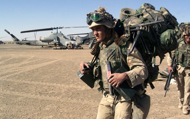 Near a US Marine Corps (USMC) AH-1W Super Cobra attack helicopter, an infantryman with the 15th Marine Expeditionary Unit (MEU) Special Operations Capable (SOC) carries a full combat load, including an FNMI 7.62 mm M240 Machine Gun, while moving into a security position after seizing a forward operating base in support of Operation ENDURING FREEDOM