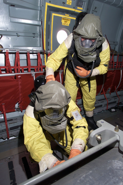 Inside a C-141 Starlifter, airmen in MCU-2P Gas Mask with self contained breathing tank and protective hood and suits at McGuire Air Force Base, New Jersey practice in preparation for an upcoming NSAV (Nuclear STAFF Assistant Visit). Personnel from headquarters will visit and observe the mission support for aircraft containing nuclear devices