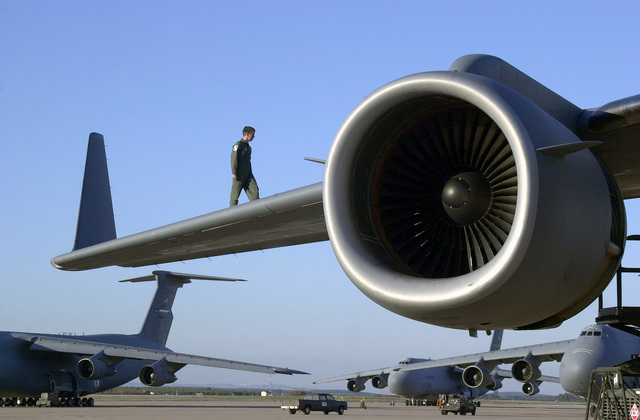 SENIOR AIRMAN (SRA) Troy Barber walks the wing of a C-17 Globemaster, as part of post-flight check at Moron Air Base, Spain, during Operation ENDURING FREEDOM